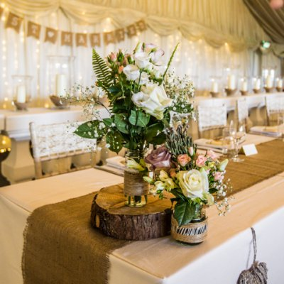 Log slices, hessian runners and gypsophila are a simple but effective creation for your tables.