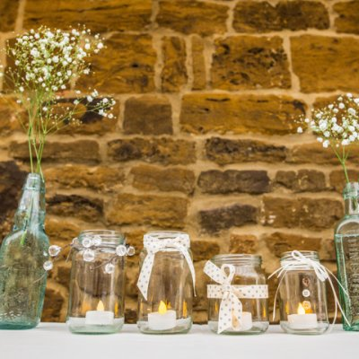 Gypsophila, tea lights and jars add to the country barn, rustic theme.