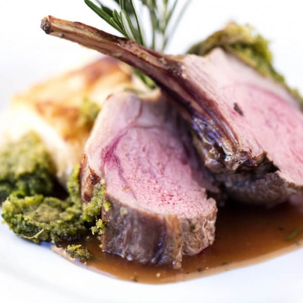 Beautifully cooked lamb with a sprig of rosemary.