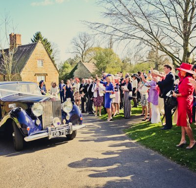 Waving the newly weds off in the Rolls Royce.