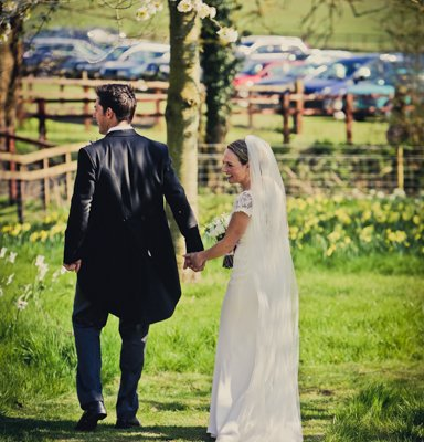 Amy & joe walk through the orchard.