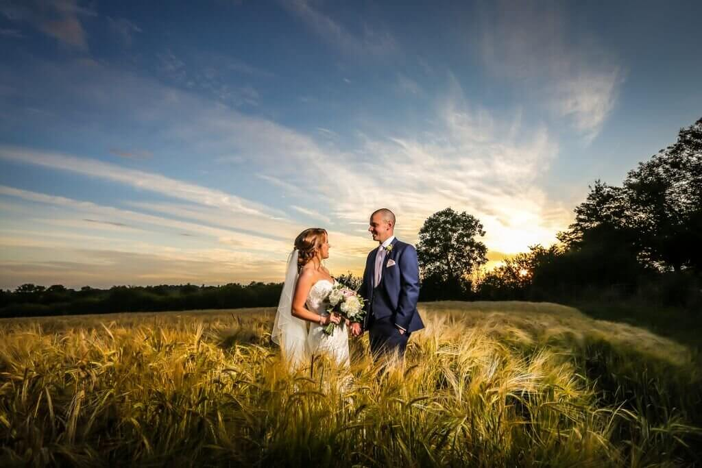 wedding photo with sunset in a field