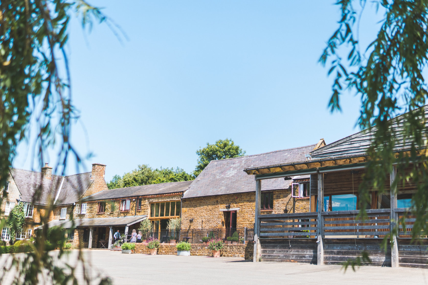 The venue at Crockwell: stone barn and farmhouse and wooden terrace.